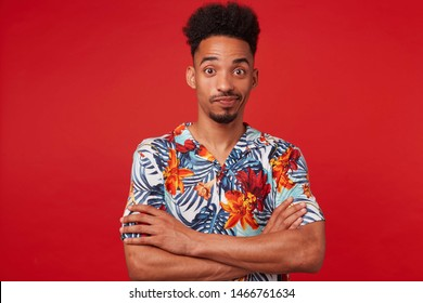 Young African American guy wears in Hawaiian shirt, looking at the camera with wondered and misunderstanding, stands over red background with crossed arms.
