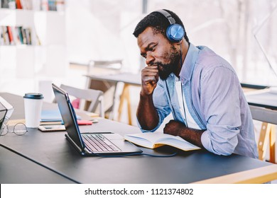 Young african american hipster guy in headphones watching online football match worried and nervous about team, african american hipster guy concentrated on training webinar learning online course