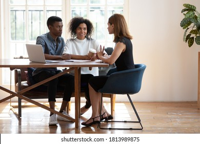 Young African American husband and wife sit at desk talk with female real estate agent discuss buying house together, biracial couple meet with designer architect or broker consult in modern office