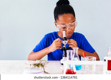 Young African American kid using microscope and experimenting scientific lab along with chemical substance tubes and flasks in classroom