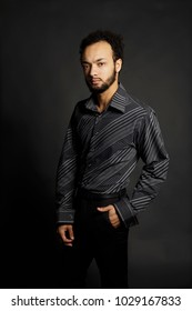 young African American male model in suit on dark background