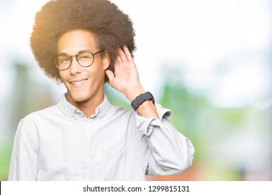 Young african american man with afro hair wearing glasses smiling with hand over ear listening an hearing to rumor or gossip. Deafness concept.