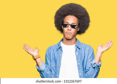 Young african american man with afro hair wearing thug life glasses clueless and confused expression with arms and hands raised. Doubt concept.