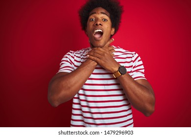 Young african american man with afro hair wearing striped t-shirt over isolated red background shouting and suffocate because painful strangle. Health problem. Asphyxiate and suicide concept.