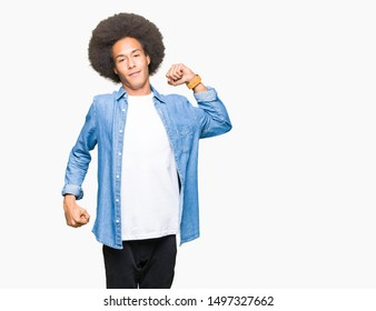 Young african american man with afro hair stretching back, tired and relaxed, sleepy and yawning for early morning