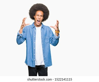 Young african american man with afro hair Shouting frustrated with rage, hands trying to strangle, yelling mad