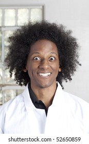 A young african american man with an afro making facial expressions while wearing a lab coat. Vertical shot.