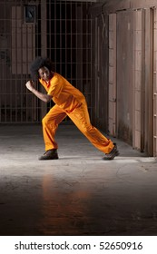 A young african american man with an afro is looking behind him as he is making an escape from a prison cell. Vertical shot.