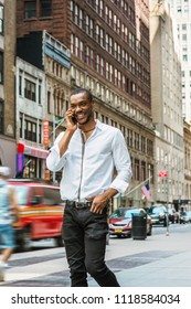 Young African American Man with beard traveling in New York, wearing white shirt, black pants, walking on street in Manhattan, talking on cell phone, smiling. Cars, buildings on background.