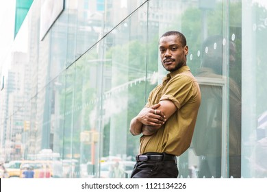Young African American Man with beard, wearing green short sleeve shirt, black pants, arms crossing in front, standing against glass wall with reflections on street in Manhattan, New York, relaxing.