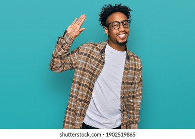 Young african american man with beard wearing casual clothes and glasses waiving saying hello happy and smiling, friendly welcome gesture