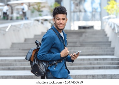 Young african american man carrying backpack walking up the stairs on city street looking back camera smiling joyful holding smartphone blurred background