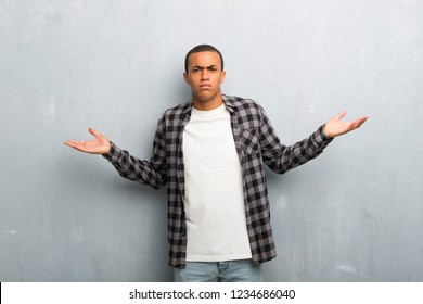 Young african american man with checkered shirt unhappy and frustrated with something because not understand something