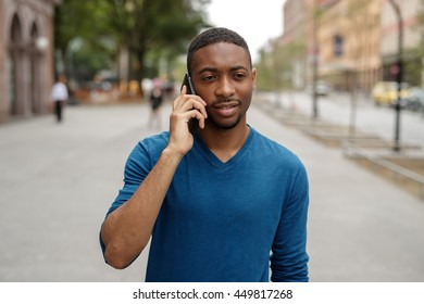 Young African American man in city walking talking cell phone
