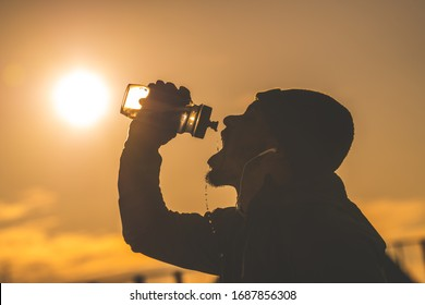 Young African American man drinking water during morning workout