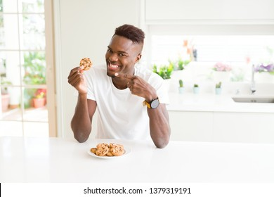 Young african american man eating chocolate chips cookies very happy pointing with hand and finger