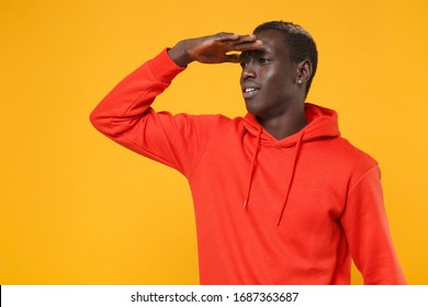 Young african american man guy in red streetwear hoodie posing isolated on yellow orange background. People lifestyle concept. Mock up copy space. Holding hand at forehead looking far away distance