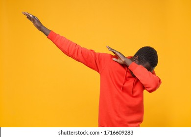 Young african american man guy in red streetwear hoodie posing isolated on yellow background studio portrait. People sincere emotions lifestyle concept. Mock up copy space. Showing DAB dance gesture