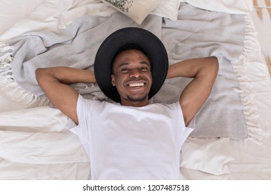 Young African American man in a hat lying on the bed.