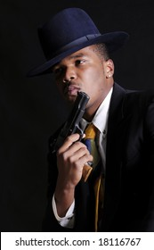 young African American man in a hat and suit with a semi-automatic pistol