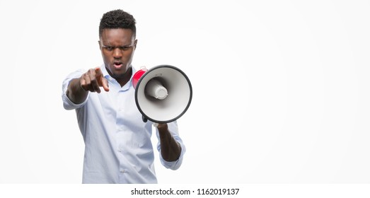 Young african american man holding megaphone pointing with finger to the camera and to you, hand sign, positive and confident gesture from the front
