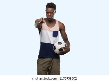 Young african american man holding soccer football ball pointing with finger to the camera and to you, hand sign, positive and confident gesture from the front