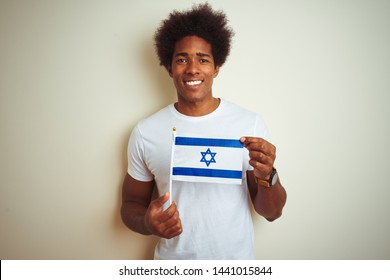 Young african american man holding Israel Israeli flag standing over isolated white background with a happy face standing and smiling with a confident smile showing teeth