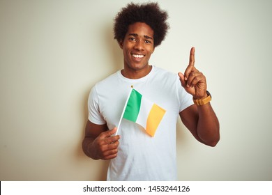 Young african american man holding Ireland Irish flag standing over isolated white background surprised with an idea or question pointing finger with happy face, number one