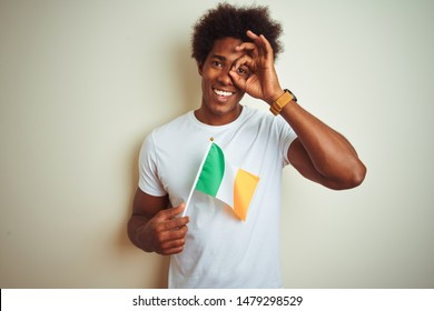 Young african american man holding Ireland Irish flag standing over isolated white background with happy face smiling doing ok sign with hand on eye looking through fingers