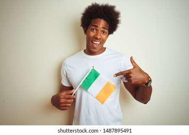 Young african american man holding Ireland Irish flag standing over isolated white background very happy pointing with hand and finger