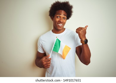 Young african american man holding Ireland Irish flag standing over isolated white background pointing and showing with thumb up to the side with happy face smiling