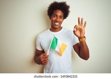 Young african american man holding Ireland Irish flag standing over isolated white background doing ok sign with fingers, excellent symbol