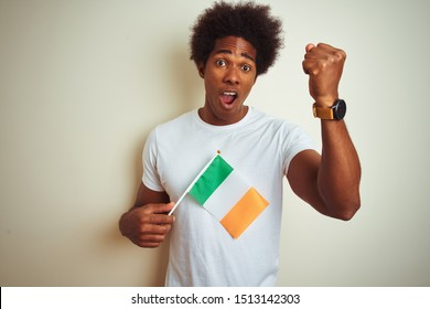 Young african american man holding Ireland Irish flag standing over isolated white background annoyed and frustrated shouting with anger, crazy and yelling with raised hand, anger concept