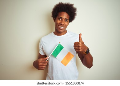 Young african american man holding Ireland Irish flag standing over isolated white background happy with big smile doing ok sign, thumb up with fingers, excellent sign