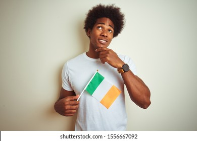 Young african american man holding Ireland Irish flag standing over isolated white background serious face thinking about question, very confused idea