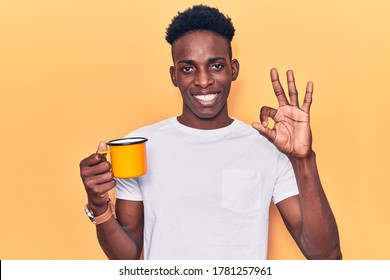 Young african american man holding coffee doing ok sign with fingers, smiling friendly gesturing excellent symbol