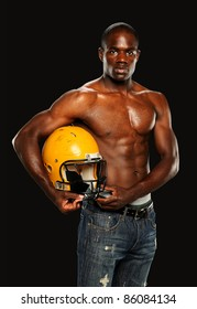 Young African American Man Holding a Football Helmet isolated on a gray background