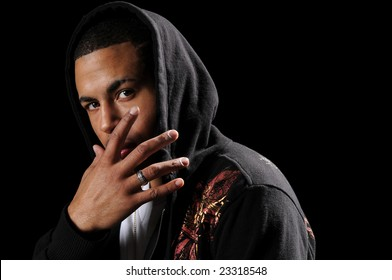 Young African American man with hood and hand in front of face