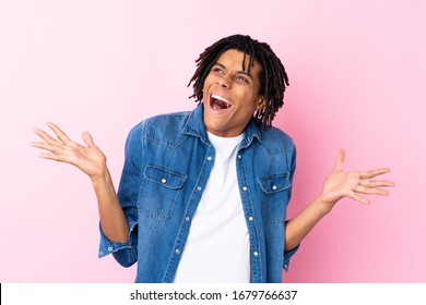 Young African American man with jean shirt over isolated pink background with surprise facial expression
