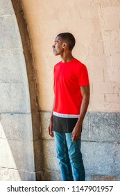 Young African American Man missing you, waiting for you in New York City, with short hair, wearing red T shirt, jeans, standing by gate with paited wall, rocks in summer, looking outside. Side View.