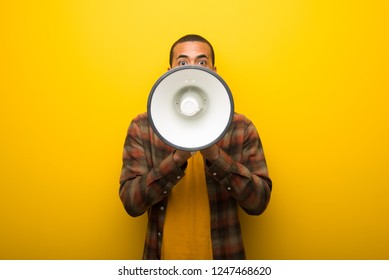 Young african american man on vibrant yellow background shouting through a megaphone to announce something