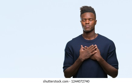 Young african american man over isolated background smiling with hands on chest with closed eyes and grateful gesture on face. Health concept.