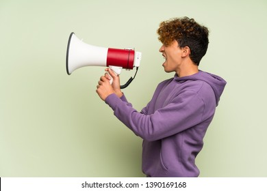 Young african american man over isolated green wall shouting through a megaphone