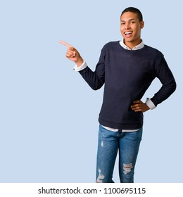 Young african american man pointing finger to the side and presenting a product on isolated blue background
