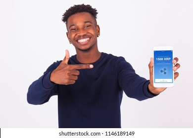 Young African American man pointing his smartphone screen  showing a received crypto currency transaction of ripple xrp received - Black teenager people