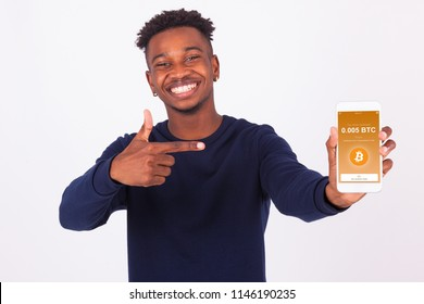 Young African American man pointing his smartphone screen  showing a received crypto currency transaction of bitcoin btc received - Black teenager people