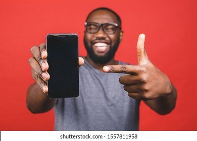 Young African American man pointing his smartphone screen isolated over red background. Black teenager people.