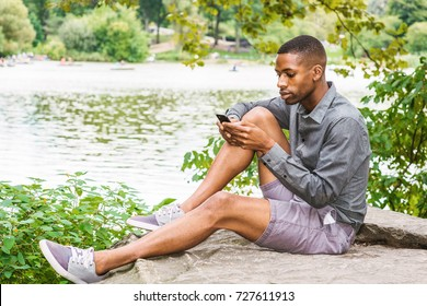 Young African American Man relaxing at Central Park in New York. Young black man wearing gray long sleeves shirt, shorts, sneakers, sitting on rocks by lake, reading, texting on cell phone.