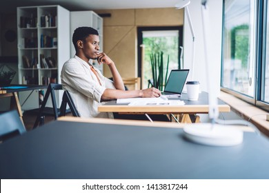 Young African American man sitting at table with laptop in office and looking thoughtfully away in window while dreaming in daylight
