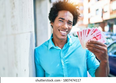 Young african american man smiling happy. Leaning on the wall with smile on face holding israeli shekels banknotes at town street.